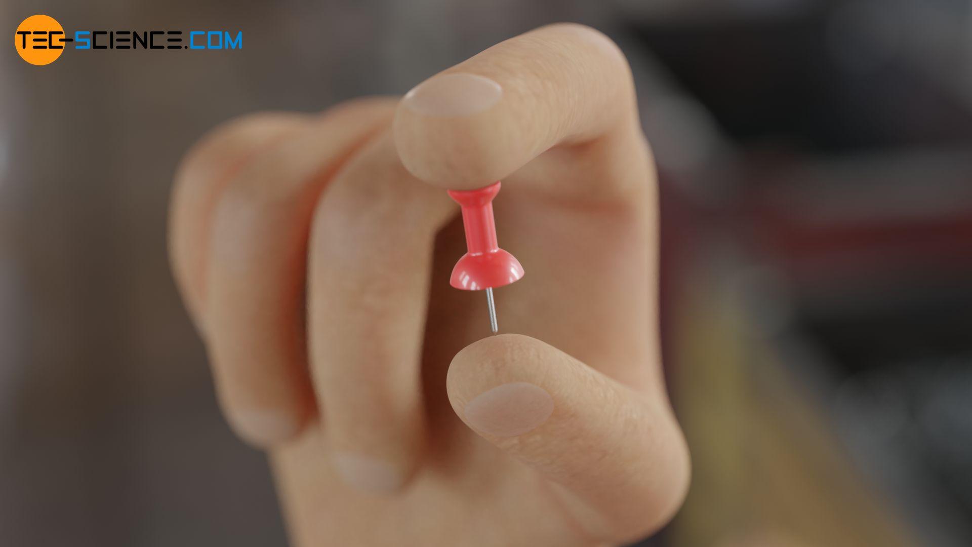 Zusammendrücken einer Reißzwecke zwischen zwei Fingern